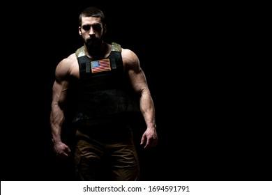 Bodybuilder Portrait of Soldier With Bulletproof Vest and Us Flag on a Black Background
