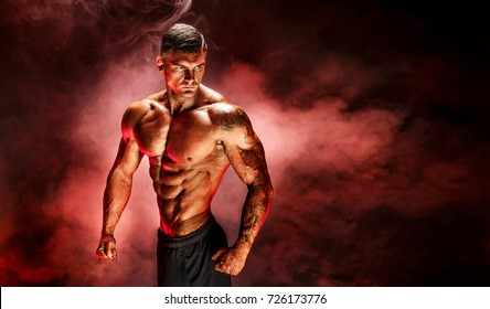Bodybuilder posing. Fitness tattooed muscled man on red smoke background. Studio shot.
