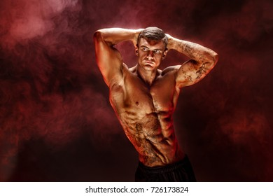 Bodybuilder posing. Fitness tattooed muscled man on red smoke background. Studio shot.