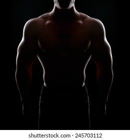 bodybuilder posing. Handsome power athletic guy male. Fitness muscular body on black background