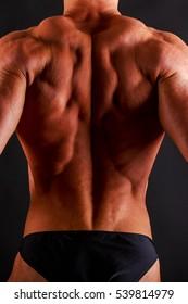 Bodybuilder posing on black