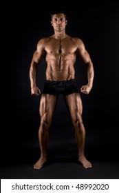 Bodybuilder posing on black background.
