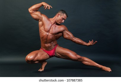 Bodybuilder posing on dark background - studio shot