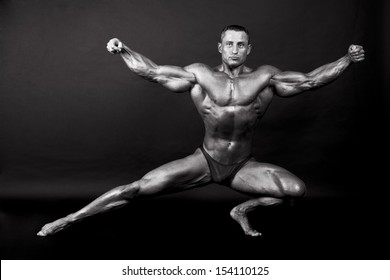 Bodybuilder posing on dark background - BW shot