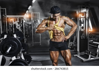 Bodybuilder professional  sportsman with big muscles demonstrates the abdominal muscles in the gym