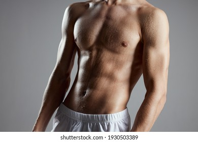 bodybuilder with a pumped-up torso on a gray background closeup