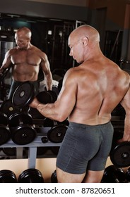 bodybuilder showing his muscles in the gym