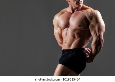 bodybuilder shows his muscles in tension on a gray background