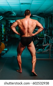 Bodybuilder stands with his back in the gym