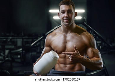 Bodybuilder strong athletic rough man with protein powder after workout workout fitness and bodybuilding healthy concept background - muscular fitness men doing exercises in gym naked torso