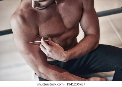 Bodybuilder, taking steroids injections in the shoulder on the background of the gym