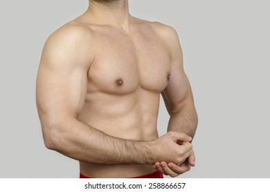 Bodybuilder topless, showing his muscles. Unrecognizable strong man with perfect abs, shoulders,biceps, triceps and chest.