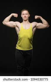 bodybuilder in t-shirt shows off double bicep in front of on a black background
