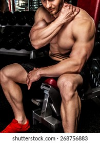 Bodybuilder warming up before training in a gym.