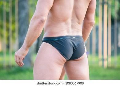 Bodybuilder wearing black swimming trunks on the beach.