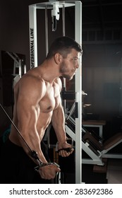 Bodybuilder Is working on his chest with cable crossover In a dark gym
