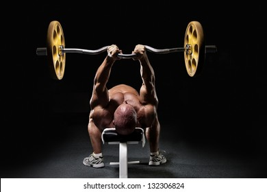 Bodybuilder working out biceps with barbell on bench from back isolated on black