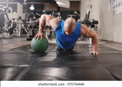bodybuilder working out and doing push upsat the gym while