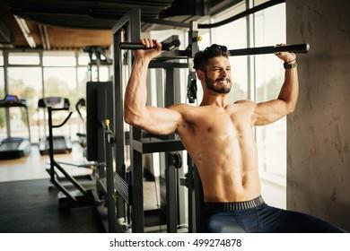 Bodybuilder working out in gym with determination