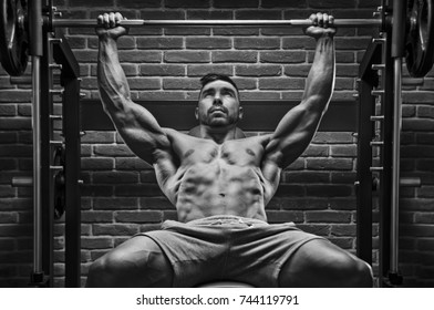 Bodybuilder workout for chest with brick wall on the background.