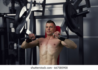 Bodybuilder workout on trainer in gym, perfect muscular male body, black and white background