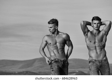 bodybuilders, athletes show sexy, muscular torsos with six packs, abs, biceps, triceps outdoor in mountains on sky, black and white