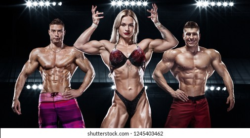 Bodybuilding competitions on the scene. Men and women sportsmens and athletes. Black background with lights.