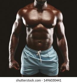 Bodybuilding concept. African american male bodybuilder showing naked torso, muscular body, studio black background