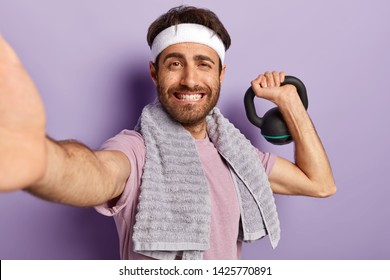 Bodybuilding concept. Glad unshaven man does sport with weight, wears headband, casual t shirt uses towel makes selfie portrait for sharing photos in social networks. Male has training with kettlebell