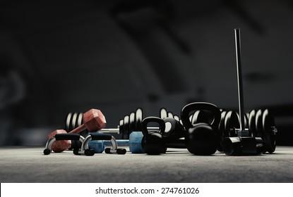 Bodybuilding equipment on concrete floor.