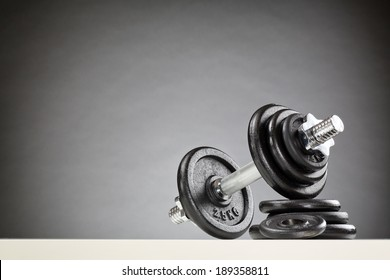 Bodybuilding or fitness equipment - a dumbbell resting on a stack of black weight discs.