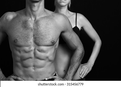 Bodybuilding, sport, fitness ,workout concept. Fit couple,  strong muscular man and slim woman posing on a black background