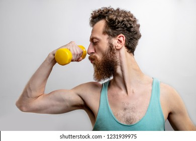 Bodybuilding and Sports concept. Skinny adult bearded man in singlet, slim mature man with anorexic body comically demonstrates his musculs with raised hands and dumbbell