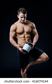 Bodybuilding and Sports theme: handsome strong bodybuilder holding plastic jar with a dry protein feeling relaxed isolated on black background in studio