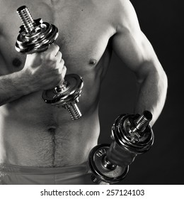 Bodybuilding. Strong fit man exercising with dumbbells. Closeup muscular young guy lifting weights black & white photo