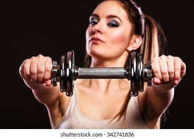 Bodybuilding. Strong fit woman exercising with dumbbells. Closeup muscular girl lifting weights on black