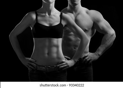 Bodybuilding. Strong man and a woman posing on a black background