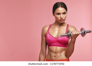Bodybuilding. Woman Training With Dumbbell On Pink Background