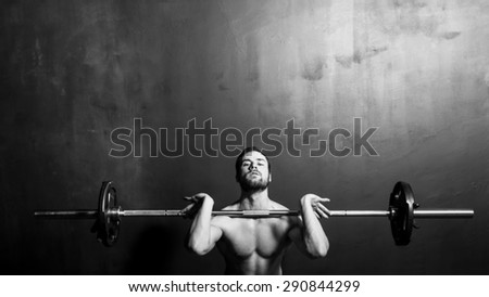 Bodybuilding, Young Athletic Strong Man Weightlifting , Black and White in studio