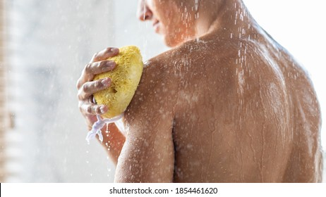 Bodycare Concept. Unrecognizable muscular man taking refreshing shower and washing his hands and shoulders with sponge, back view. Guy standing in the bathroom under falling hot water drops