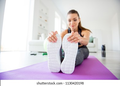 Bodycare first medical aid suffer symptom acute concept. Low angle close up view photo of pretty sporty sportive positive trainer coach instructor touching feet resting on carpet window nice manicure