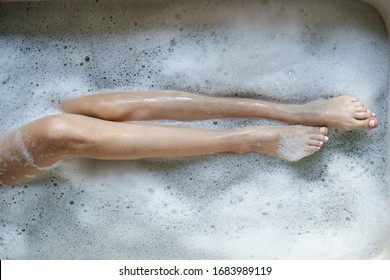 Bodycare and skincare concept. High angle and cropped view of young adult girl holding legs over foam water and taking bath at home