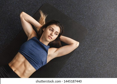Bodycare, sports and workout concept. Motivated sportswoman working hard on getting abs, muscles fit, lying black rubber mat gym floor, warm-up training session, doing fitness bicycle crunches