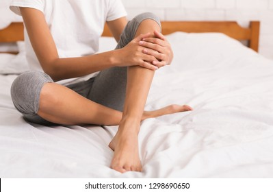 Bodycare. Woman with bare legs sitting on bed at home, crop, copy space