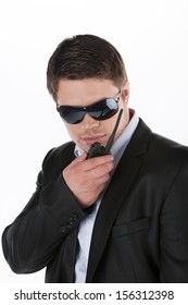 Bodyguard. Confident young man in sunglasses talking on radio while standing isolated on white