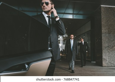 bodyguard opening car door for businessman