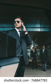 bodyguard opening car door for businessman and listening security earpiece