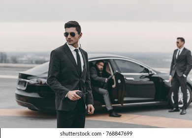 bodyguard with portable radio standing at businessman car