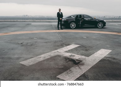 bodyguard standing close to businessman car on helipad