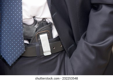 Bodyguard in a suite with a tie and a pistol